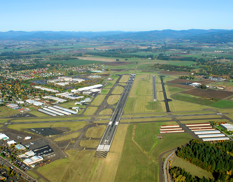 An aerial view of the Hillsboro Airport shows linear runways in a green field.